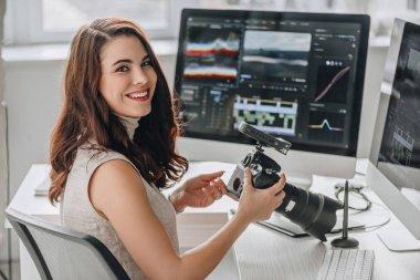cheerful art editor holding digital camera near table with computer monitors