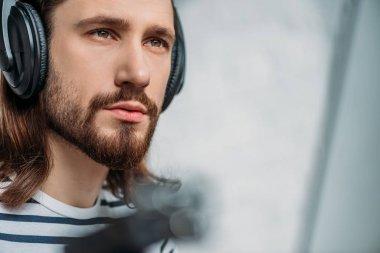handsome bearded editor listening music in headphones