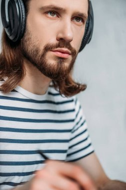 Selective focus of handsome bearded editor listening music in headphones stock vector