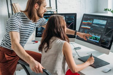 bearded art editor pointing with finger at computer monitor near woman