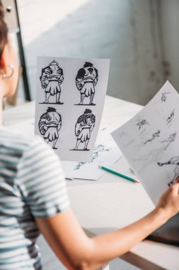 selective focus of illustrator holding papers with sketches