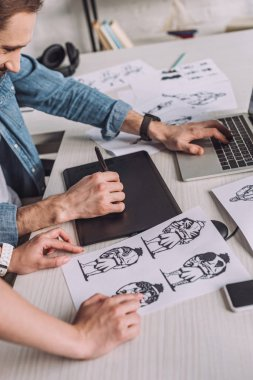cropped view of animator pointing with finger at cartoon sketch near coworker