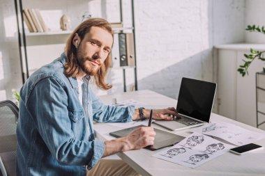 bearded of animator in wireless earphones near gadgets