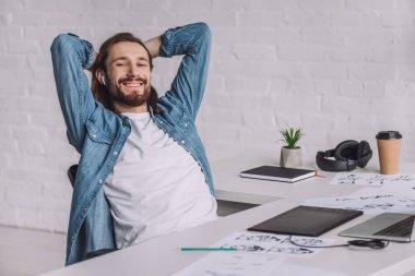 cheerful illustrator in wireless earphones near sketches on table