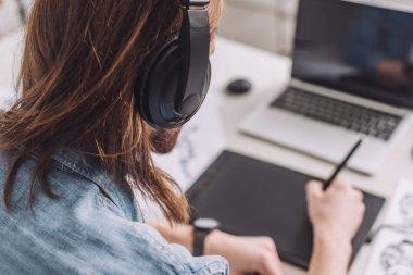 selective focus of animator listening music in headphones