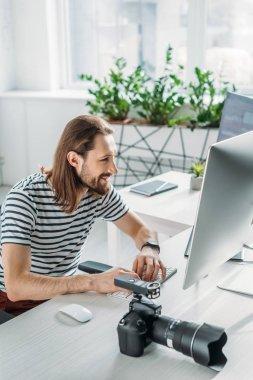 happy and bearded editor working near digital camera in studio
