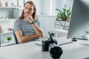selective focus of pensive art editor thinking near digital camera