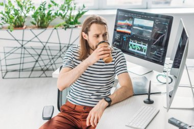 art editor looking at computer monitor while drinking coffee to go