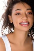 usmívající se africká americká dívka se zubními rovnátky, izolovaná na bílém