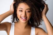 Fotografie schöne positive afrikanische Amerikanerin mit Zahnspange, isoliert auf grau
