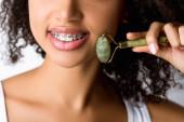 Ausgeschnittene Ansicht eines lächelnden afrikanisch-amerikanischen Mädchens mit Zahnspange mit natürlicher Massagerolle, isoliert auf grau