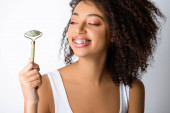 Fotografie glücklich afrikanisch-amerikanische Mädchen mit Zahnspange mit natürlichen Massagerolle, isoliert auf grau