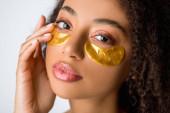 atraktivní brunetka africký americký dívka se zlatými pásky přes oko, izolované na šedé