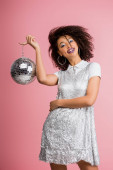 cheerful african american girl in paillettes dress holding disco ball, isolated on pink