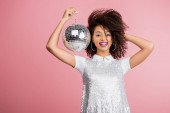 smiling african american girl in paillettes dress holding disco ball, isolated on pink