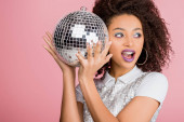 excited african american girl in paillettes dress holding disco ball, isolated on pink