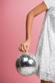 cropped view of african american girl in paillettes dress holding disco ball, isolated on pink