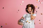 sokkolt afro-amerikai lány paillette ruha kezében disco labda, elszigetelt rózsaszín konfettivel