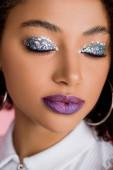 africká americká dívka se stříbrnými třpytivými očními stíny na zavřených očích a purpurovými rty, izolovaná na růžové