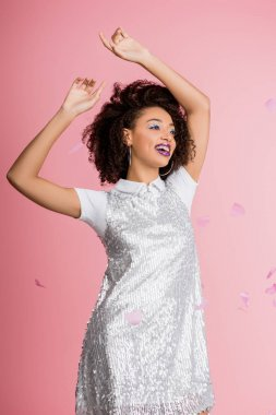 Attractive happy african american girl with dental braces, with silver glitter eyeshadows and purple lips dancing in paillettes dress, isolated on pink with confetti stock vector
