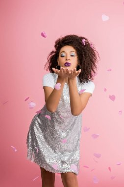 happy african american girl with silver glitter eyeshadows and purple lips wearing paillettes dress and blowing air kiss, isolated on pink with confetti