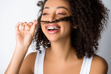 laughing african american girl with dental braces making fake mustache from hair, isolated on grey