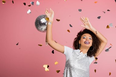 Excited african american girl in paillettes dress dancing with disco ball, isolated on pink with confetti stock vector