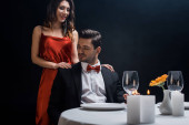 Beautiful smiling woman standing beside handsome man in suit at served table isolated on black