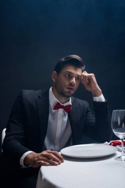 Handsome man in suit looking away at served table isolated on black stock vector