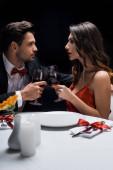 Boční pohled na elegantní pár při pohledu na sebe při cinkání s vínem u servírovaného stolu izolované na černé