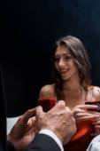 Photo Selective focus of man holding box with jewelry by smiling woman with wine glass isolated on black