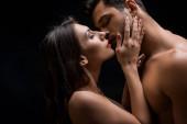Boční pohled krásné nahé ženy líbání bez trička muž izolovaný na černé