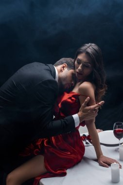Side view of handsome man taking off dress of sexy woman during romantic dinner on black background with smoke stock vector