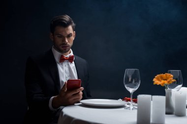Elegant man looking at smartphone at served table with candles on black background with smoke stock vector