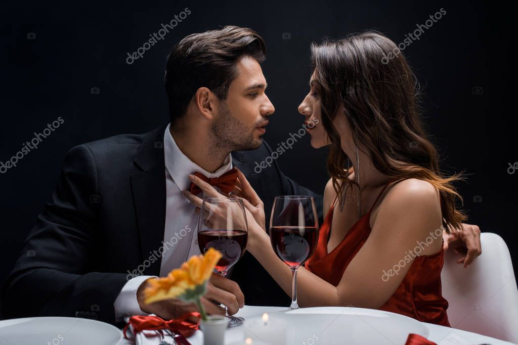 Side view of beautiful woman adjusting bow tie of handsome man during romantic dinner isolated on black stock vector
