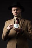 elegáns férfi bézs öltönyben, kalap és szemüveg tartó csésze és csészealj elszigetelt fekete