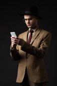 seriózní elegantní muž v béžovém obleku, klobouku a brýlích pomocí chytrého telefonu izolovaného na černé