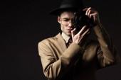 elegáns férfi bézs öltönyben, kalap és szemüveg fotózás film kamera elszigetelt fekete