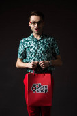 Photo shocked fashionable man in eyeglasses in blue colorful shirt and red pants holding red shopping bag from sex shop isolated on black