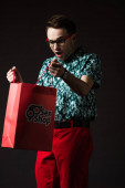 Photo shocked fashionable man in eyeglasses in blue colorful shirt and red pants looking in red shopping bag from sex shop isolated on black