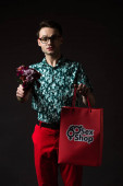 Photo smiling fashionable man in eyeglasses in blue colorful shirt and red pants holding red shopping bag from sex shop and flowers isolated on black