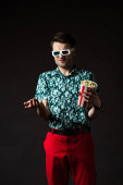 confused fashionable man in 3d glasses in blue colorful shirt and red pants holding popcorn isolated on black