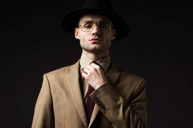 Elegant man in beige suit, hat and eyeglasses fixing tie isolated on black stock vector
