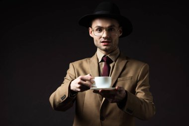 Excited elegant man in beige suit, hat and eyeglasses holding coffee cup and saucer isolated on black stock vector