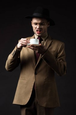 displeased elegant man in beige suit, hat and eyeglasses holding coffee cup and saucer isolated on black
