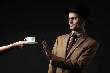 elegant man in beige suit, hat and eyeglasses refusing coffee from waiter isolated on black