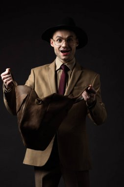 Happy elegant man in beige suit, hat and eyeglasses looking in brown leather bag isolated on black stock vector