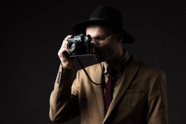 Elegant man in beige suit, hat and eyeglasses taking picture on film camera isolated on black stock vector