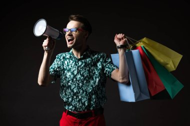 Fashionable man in eyeglasses in blue colorful shirt and red pants with shopping bags shouting in loudspeaker isolated on black stock vector