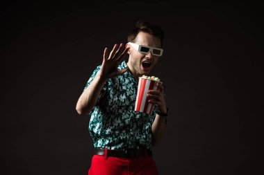Scared fashionable man in 3d glasses in blue colorful shirt and red pants holding popcorn isolated on black stock vector